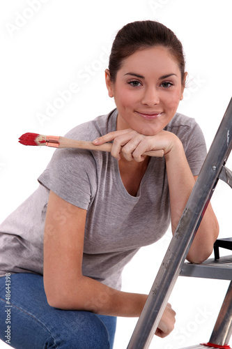 Woman with paint brush leaning on a ladder