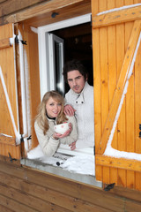 Couple at a window of a cottage