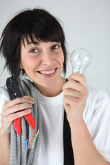 Female electrician holding replacement wiring and bulb