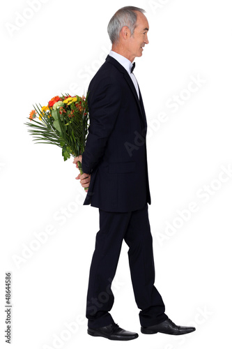 Man in an evening suit with a bouquet of flowers
