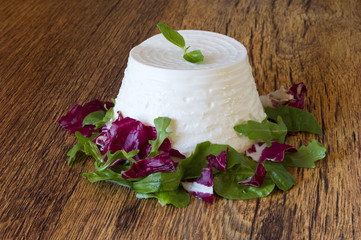 fresh ricotta with basil leaf on wooden table