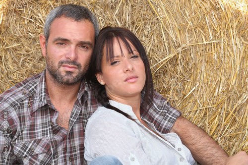 Couple leaning on haystack
