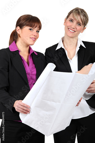 Two women holding plans