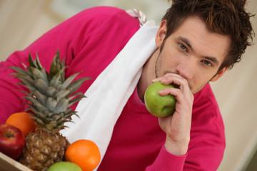 Pensive young man eating fruit