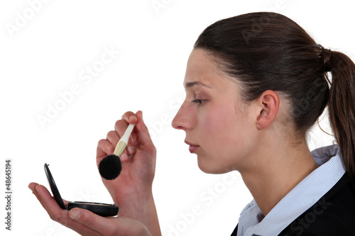 Businesswoman putting on makeup