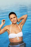 Attractive brunette in swimming pool scratching neck