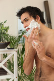 Young man applying shaving cream