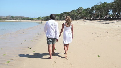 Rear view of happy man and woman walking together at coastline