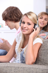 Blond teenagers wearing headphones