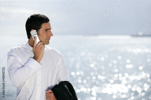 Businessman stood by the sea