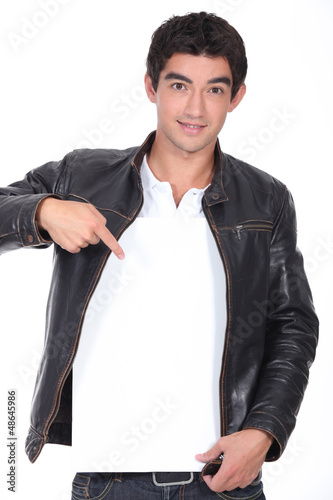 Man in leather jacket pointing at blank message board