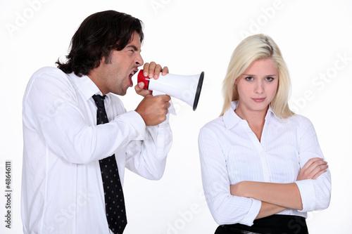 Man shouting into a woman's ear