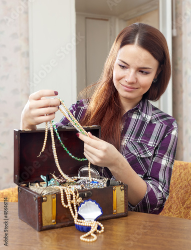pretty girl chooses jewelry in treasure chest