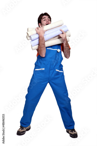 Man laden with rolls of wallpaper
