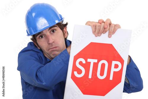builder in jumpsuit holding stop sign