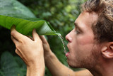 Survival - man drinking from leaf in jungle