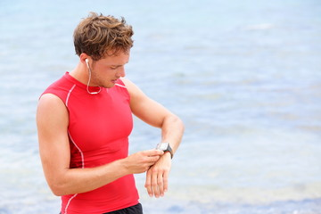 Athlete runner looking at heart rate monitor watch