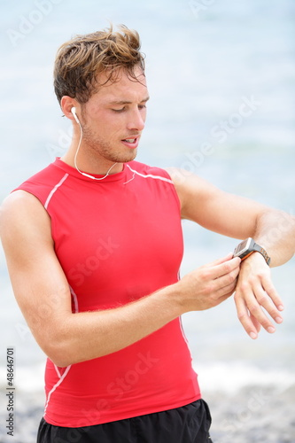 Running man looking at heart rate monitor