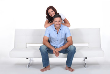 Smiling couple on a sofa, studio shot