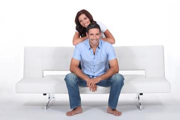 Smiling couple on a sofa, studio shot
