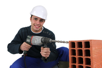 Man drilling hole in aerating brick