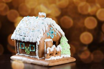 Gingerbread house over defocused glittering lights background