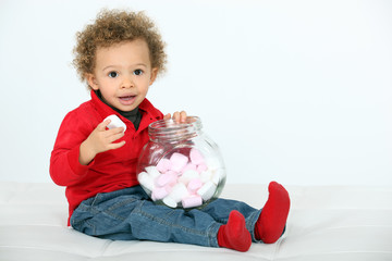Cute little boy eating marshmallows, studio shot