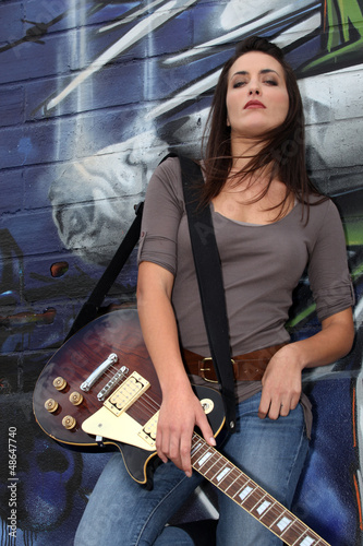 Cool female guitarist standing against graffiti