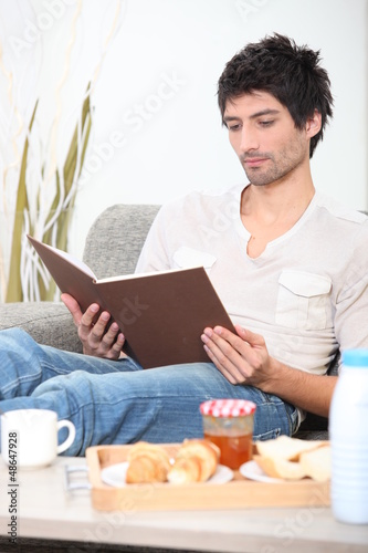Man reading book whilst eating breakfast