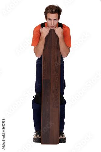 Man stood with plank of laminate flooring