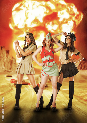 Three military females standing near nuke explosion