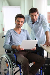 Man in wheelchair holding laptop