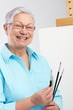 Active pensioner with paintbrush and canvas
