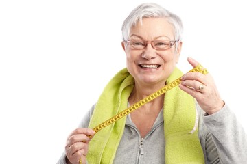 Fit old lady with tape measure smiling