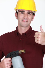 craftsman holding a welding torch and making thumbs up sign