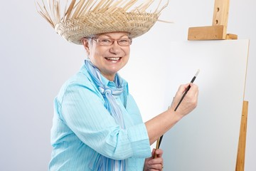 Happy old lady with canvas and paintbrush