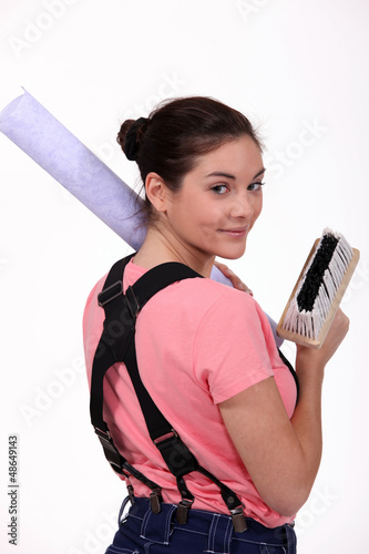 Woman carrying roll of wallpaper and brush
