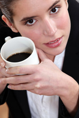 Close-up picture of a woman drinking coffee.