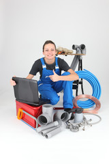 Female plumber with tools of the trade and a laptop computer