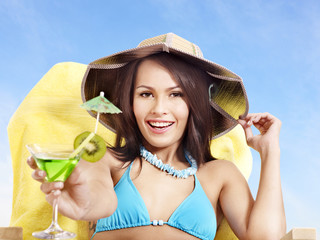 Girl in bikini drinking alcohol coctail through a straw.