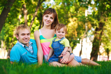 baby with parents in a beautiful summer park