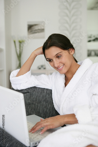 Brunette in bathing robe using laptop computer