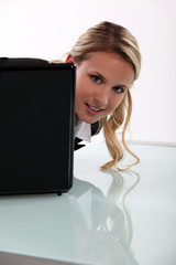 Young woman peering around her laptop