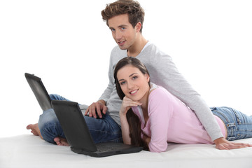 Couple laying down with two laptops