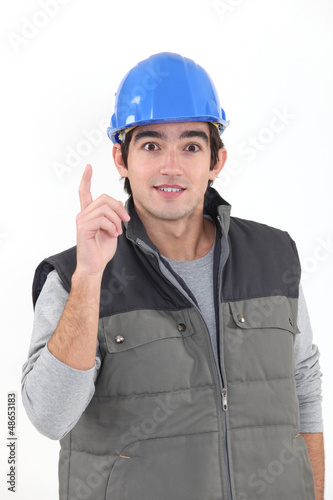 A young construction worker raising his finger.