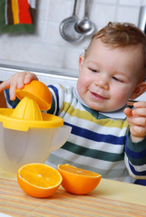 Pequeño niño exprimiendo jugo de naranja.
