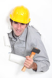 Male builder bursting through paper