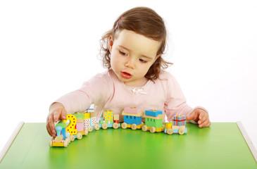 Ein Mädchen spielt mit einer Holzeisenbahn
