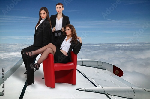 sexy businesswomen flying on a plane wing