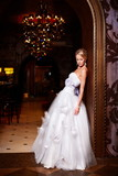 sexy blond bride in white wedding dress in interior